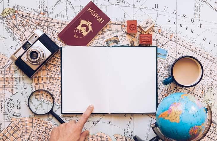 putnik pokazuje prstom na rokovnik i mapu