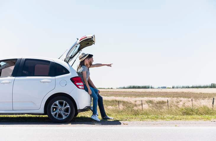 Čovek stoji naslonjen na gepek automobila