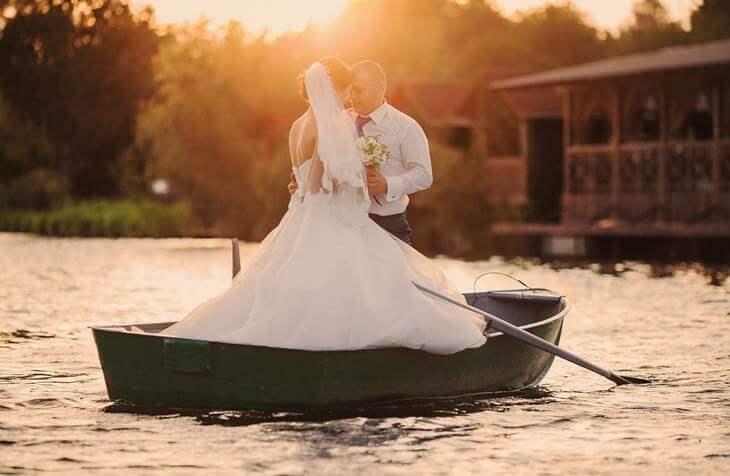Mladenci stoje u čamcu na reci