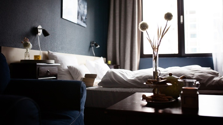 Krevet u spavaoj sobi sa tamnim enterijerom