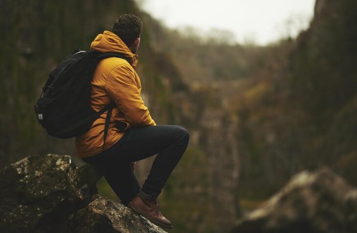 Čovek u šumi koji sedi na steni