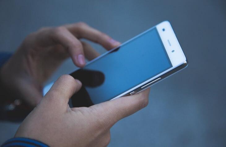 Beli tač mobilni u rukama