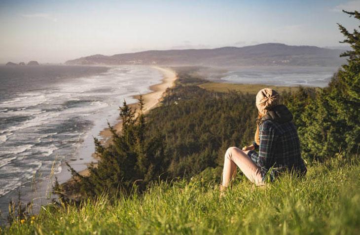 Žena sedi na travi i gleda na more i planine