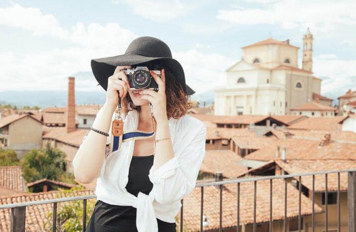 Žena sa šeširom na vidikovcu iznad krovova slika fotoaparatom