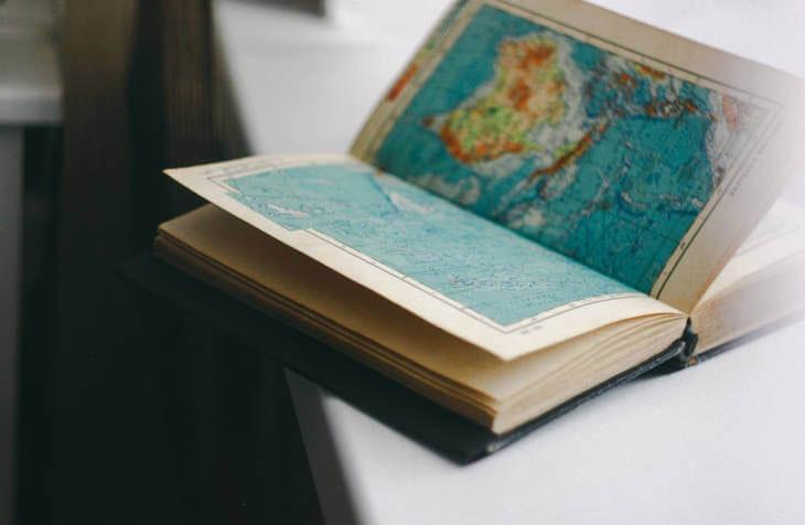 Otvorena knjiga atlas sveta na stolu