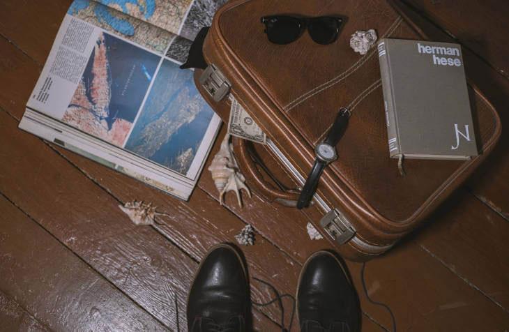 Na podu sobe pobacane knjige, kofer i knjige pored cipela