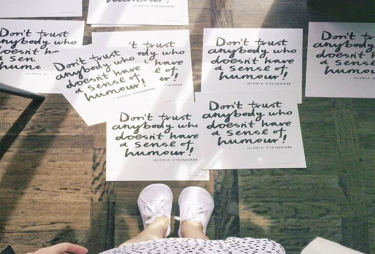 papiri sa napisanim citatima na drvenom podu i devojka koja stoji u belim patikama