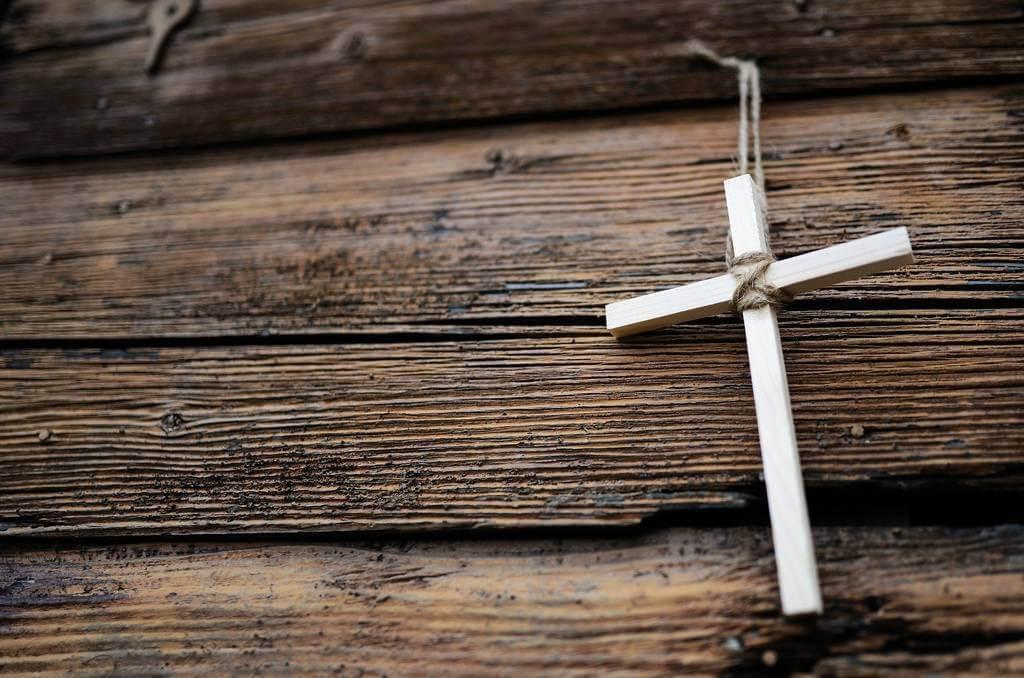 ogrlica sa krstom na drvenoj podlozi