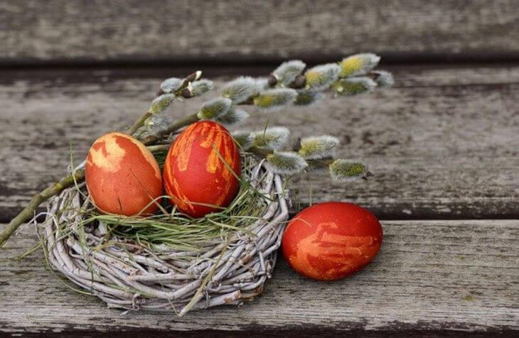 tri obojena uskršnja jaja i dekoracija na stolu