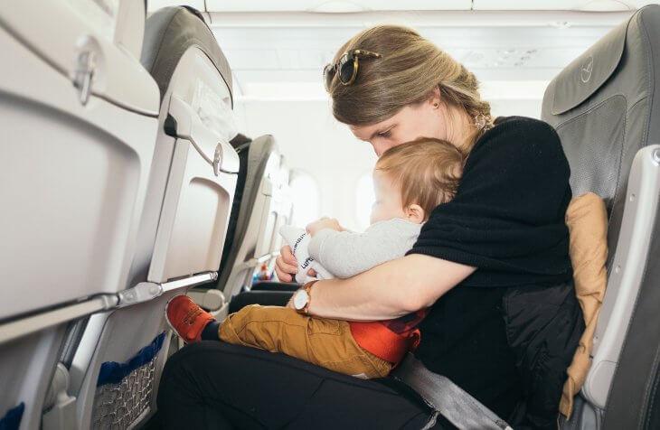 žena sa bebom u naručju u avionu