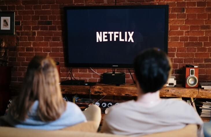 muškarac i devojka sede na dvosedu u dnevnoj sobi i gledaju seriju
