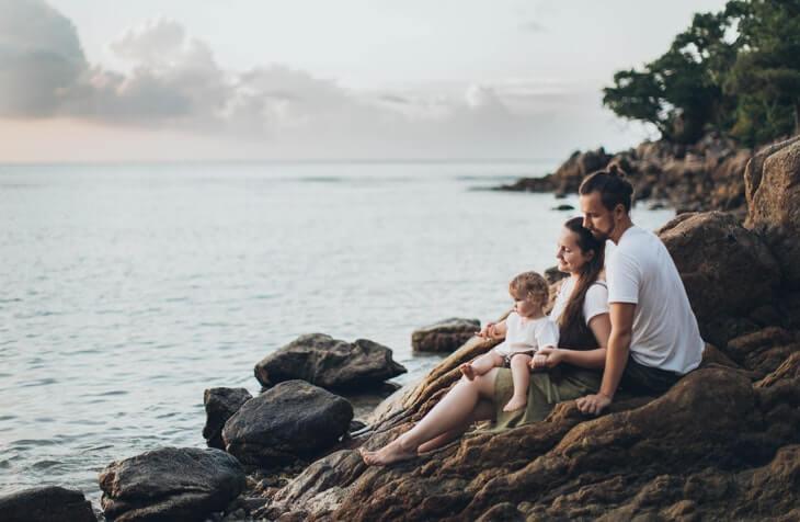 mladi par sa bebom na stenovitoj obali mora